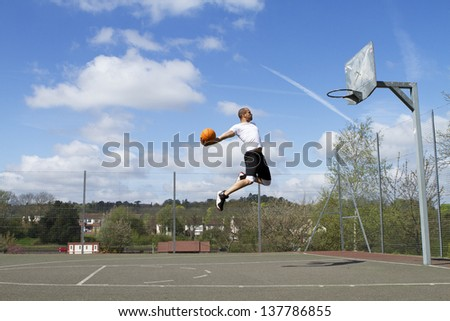 Portrait of a Basketball Player in mid air about to Slam Dunk - stock photo