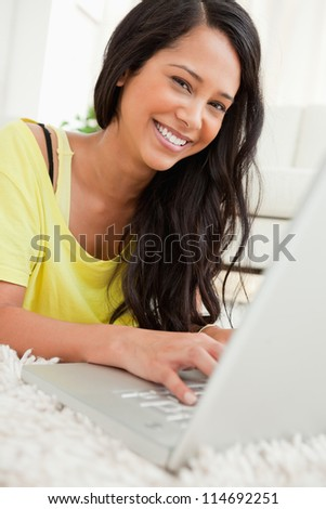 Portrait of a beaming Latin chatting on a laptop while lying on the floor