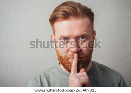 portrait of a bearded man put his finger to his lips - stock photo