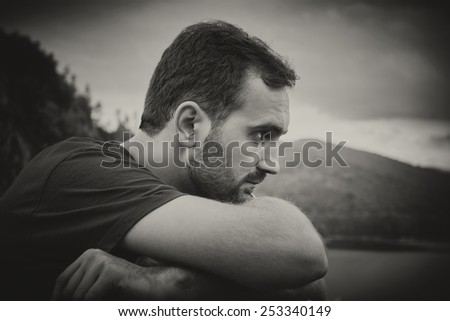 Portrait of a bearded man, wearing a red shirt and hands resting on a railing between the mountains. Black & white picture. - stock photo
