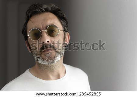 Portrait of a bearded man with sunglasses and earrings looking at camera. Selective focus. - stock photo