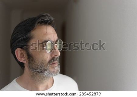 Portrait of a bearded man with sunglasses looking at one side. Selective focus. - stock photo