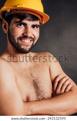 Portrait of a bearded smiling worker wearing a hard hat - isolated on black. - stock photo