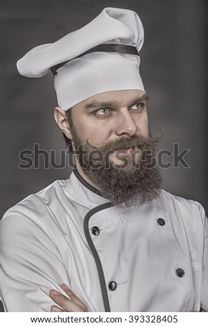 Portrait of a bearded young chef with arms folded over gray background
