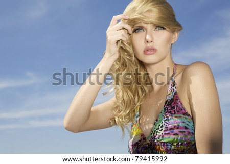 portrait of a beautiful adult sensuality blonde woman on blue sky background. copy space