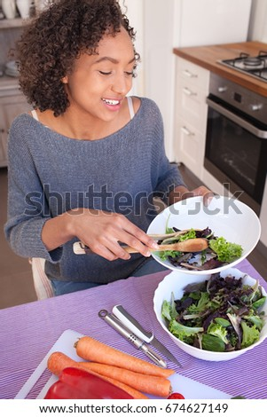 Portrait of a beautiful african american girl serving green salad leaves, eating vegetables in home kitchen, smiling indoors. Young black woman cooking healthy vegan food, lifestyle in home interior.