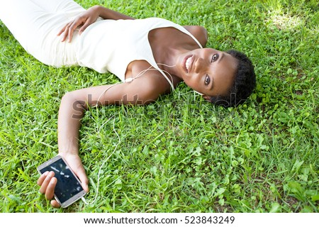 Portrait of a beautiful african american woman laying on green grass in park using smart phone technology and headphones to listen to music, relaxing smiling, looking. Black woman lifestyle, outdoors.