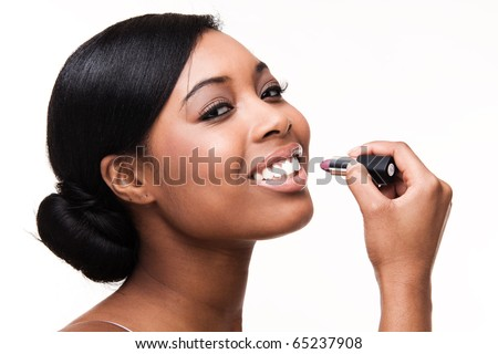Portrait of a beautiful african black woman getting ready applying lipstick