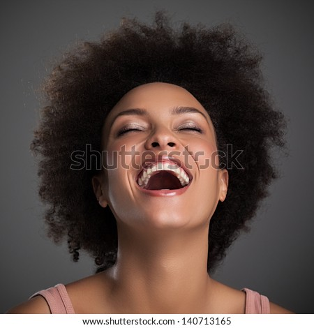 Portrait of a beautiful African woman laughing. - stock photo