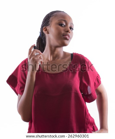 portrait of a beautiful African woman whith braids in a red shirt spraying perfume on her body while posing on an isolated background - stock photo