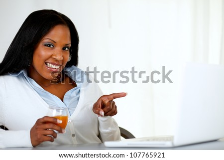 Portrait of a beautiful afro-american woman pointing the laptop screen at soft colors composition - stock photo