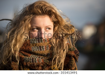 Portrait of a beautiful alternative young blonde girl with dreadlocks and a heavy scarf and a cityscape background - stock photo