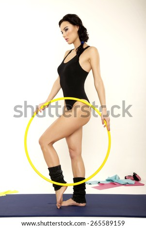 Portrait of a beautiful and attractive sexy and sensuality young adult sporty brunette woman in black dress slim body with yellow hula hoop isolated on white background - stock photo