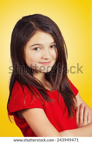 Portrait of a beautiful and confident  little girl looking to camera isolated on yellow background.