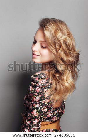 Portrait of a beautiful and gentle blonde girl in the studio on a gray background, the concept of beauty and health - stock photo