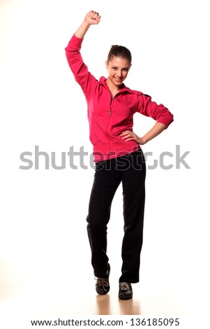 portrait of a beautiful and smiling teenage girl in tracksuits with hand up - stock photo