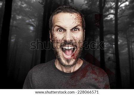 portrait of a beautiful angry male vampire on a dark forest background - stock photo