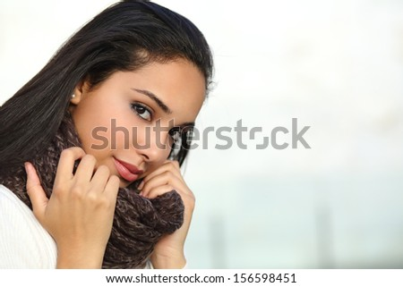 Portrait of a beautiful arab woman face warmly clothed and grabbing a scarf outdoor     - stock photo