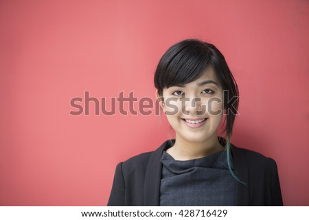 Portrait of a beautiful Asian businesswoman in smart business suit leaning against a red wall.  - stock photo