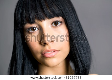 Portrait of a beautiful asian woman on a gray background - stock photo