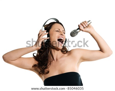 Portrait of a beautiful Asian woman with microphone and headphones singing in studio isolated on white background - stock photo