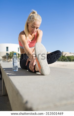 Portrait of a beautiful athletic female stretching legs muscles while sitting on concrete pier in summer day, young fit woman doing warm up exercises before begin morning run in the fresh air  - stock photo