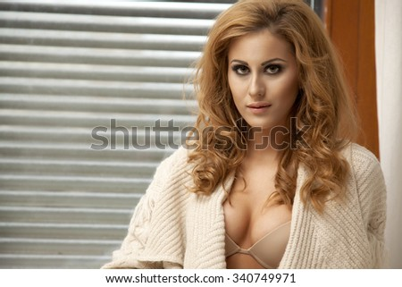 Portrait of a beautiful attractive and sexy young adult sensuality pretty blonde woman in  brown sweater
