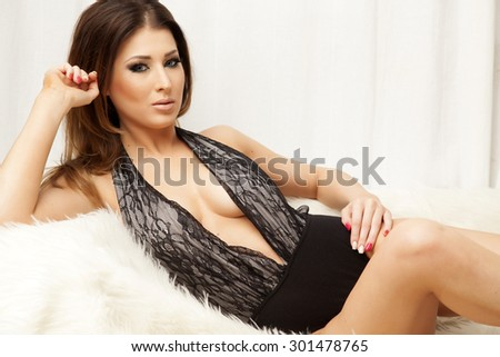 Portrait of a beautiful attractive and sexy young adult sensuality pretty brunette woman in black lingerie on the white couch on luxury apartment - stock photo