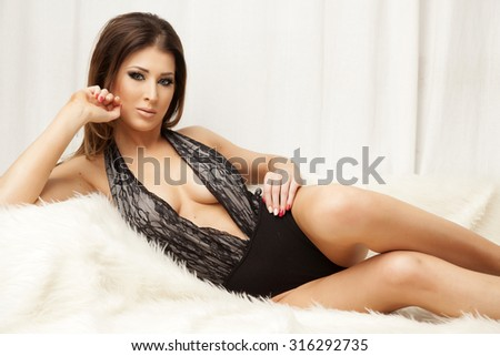 Portrait of a beautiful attractive and sexy young adult sensuality pretty brunette woman in black lingerie on the white couch and fur on luxury apartment - stock photo