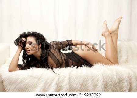 Portrait of a beautiful attractive and sexy young adult sensuality pretty brunette woman in black erotic lingerie on the white sofa and fur in luxury apartment