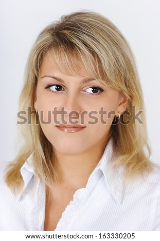 Portrait of a beautiful attractive blonde in a white blouse - stock photo