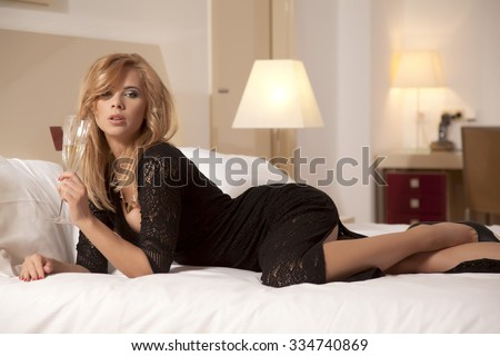 Portrait of a beautiful attractive sensuality and sexy young adult pretty babe blonde woman wearing elegance fashionable dress lying on the bed in bedroom  - stock photo