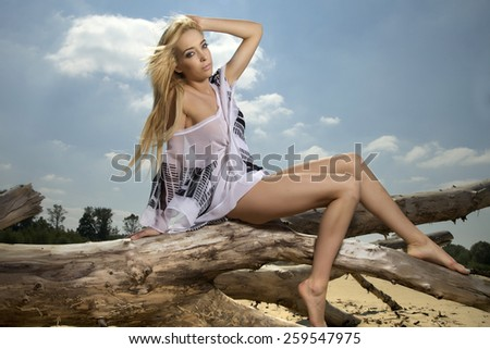 Portrait of a beautiful attractive sensuality young adult sexy pretty blonde woman in white shirt posing on a sunlight beach in summertime