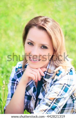 Portrait of a beautiful attractive woman in the grass on the nature