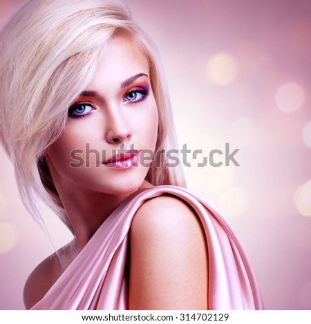 Portrait of a beautiful attractive woman with pink silk posing at creative background. - stock photo