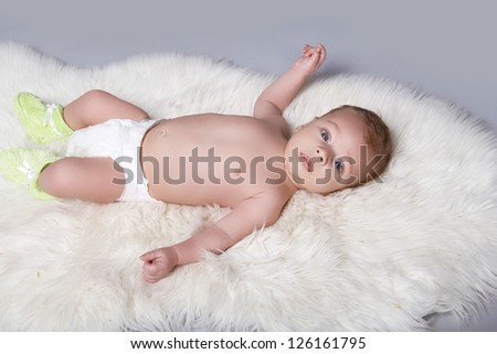 Portrait of a beautiful baby boy on fur coat background - stock photo