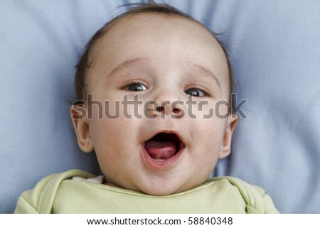 Portrait of a beautiful baby boy with a big smile and he's tong out, laying on a blue pillow wearing a green top. - stock photo