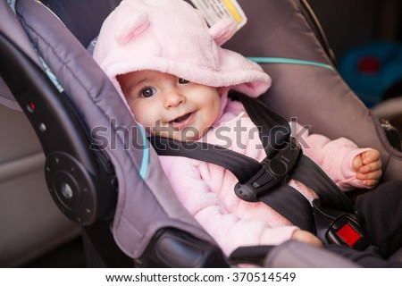Portrait of a beautiful baby girl sitting on a car seat and smiling - stock photo