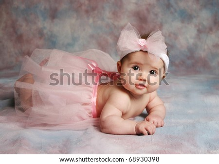Portrait of a beautiful baby girl wearing a pink ballet tutu and pink hair bow headband - stock photo