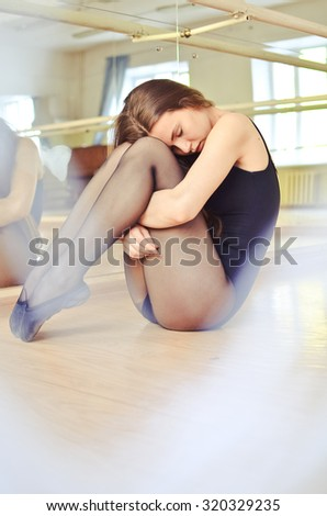 portrait of a beautiful ballerina stretching and doing exercises in ballet hall - stock photo