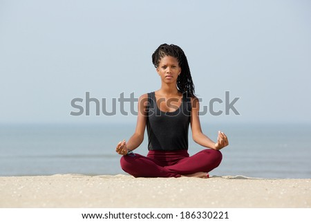 Portrait of a beautiful black woman sitting in yoga lotus pose at the beach - stock photo