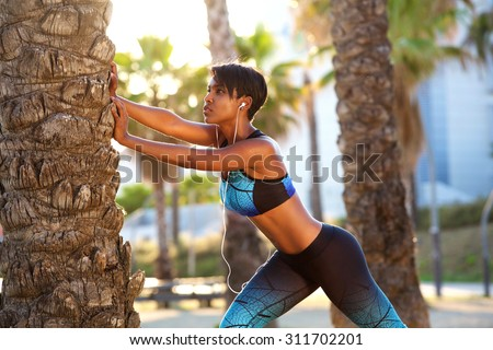 Portrait of a beautiful black woman stretching workout routine - stock photo