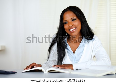 Portrait of a beautiful black woman studying at soft colors composition - stock photo