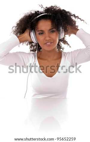 Portrait of a beautiful black woman with headphones listening to music in the studio - stock photo