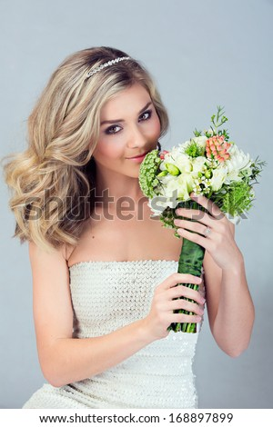 Portrait of a beautiful blond bride with a diamante headpiece. Hair in loose curly style. Wearing sequin modern dress  - stock photo