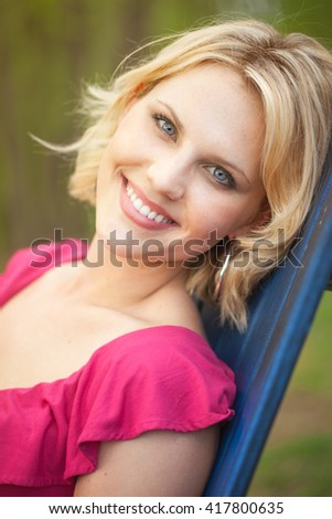 Portrait of a beautiful blond early 30s woman in a spring garden relaxing and reclining in a chair - stock photo