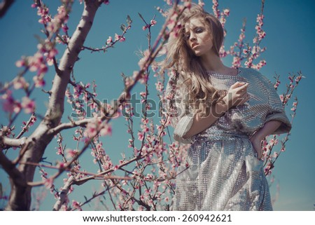Portrait of a beautiful blond girl in a silver dress, posing in a flowering cherry orchard - stock photo