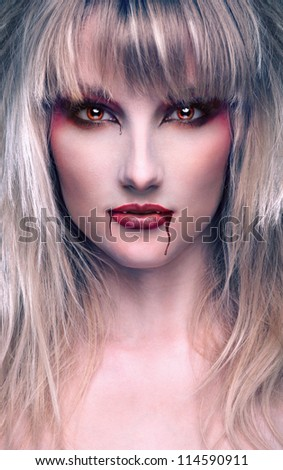 portrait of a beautiful blond girl vaprire with bloody streaks - stock photo