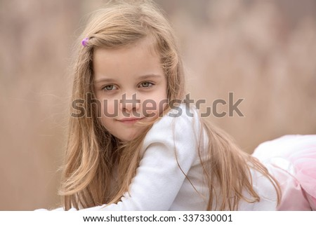 portrait of a beautiful blond girl with long hair laying outside - stock photo