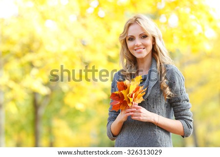 Portrait of a beautiful blond smiling woman in autumn forest - stock photo